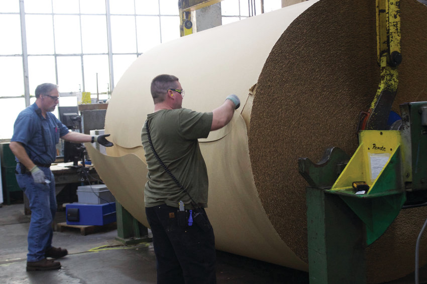 Millworkers Bob Cameron, left, and Dennis O'Keefe trim the edge of a roll of paper that has been processed at the mill.