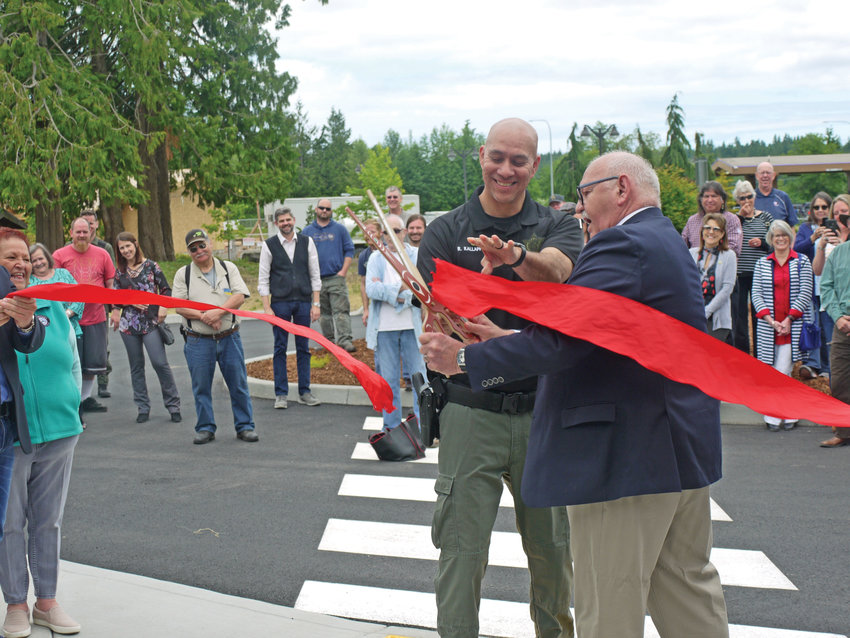 Jamestown S'Klallam Chairman and CEO W. Ron Allen cuts the ribbon on the new justice center with the help of Lead Fish and Game Enforcement Officer Rory Kallappa.