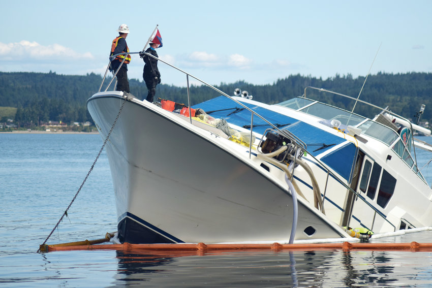 Salvage team members negotiate the steep list on the yacht that sank Tuesday afternoon south of Hood Canal Bridge. The Silver Lining yacht struck a reef of rocks called the Sisters. The eight people aboard — the boat owners, their children and grandchildren, aged 4 to 9 — escaped on an onboard skiff.