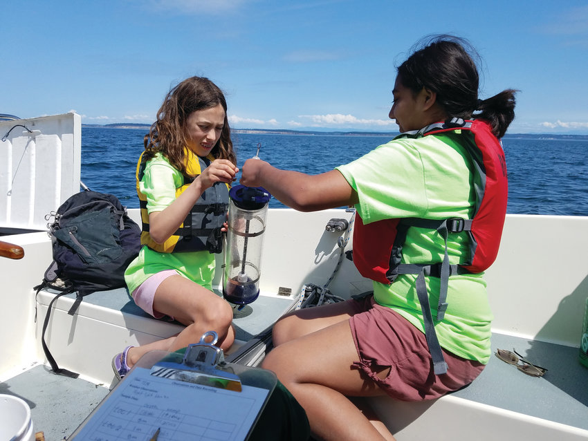 Clara Wiley and Shelby Brzycki prepare to lower the Van Dorn water sampling bottle to collect seawater samples from different depths.