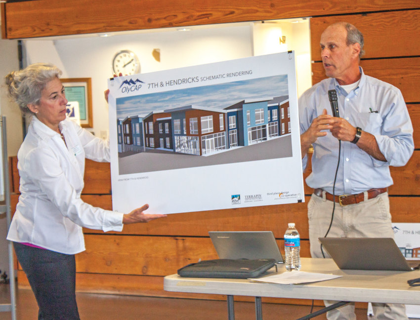 From left, Liz Coker helps Mark Blatter, of the Washington Low-Income Housing Alliance, present a conceptual illustration of OlyCAP's proposed affordable housing project Aug. 16.
