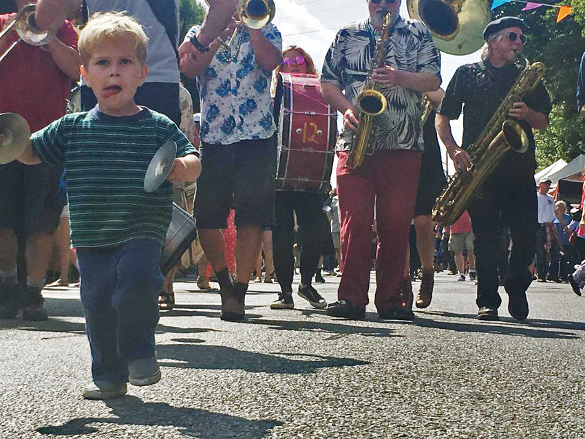 Cybalism, not semiotics, is the dominant paradigm for the Unexpected Brass Band, who feature Rigel Orr, shown here marching in the Local Grandly Parade as part of the Aug. 17 Uptown Street Fair & Parade. He's the youngest member of Port Townsend's own street orchestra. The tongue, by the way, is usually a sign a child is concentrating hard. There's some link between verbal and motor skills that triggers this common gesture.
