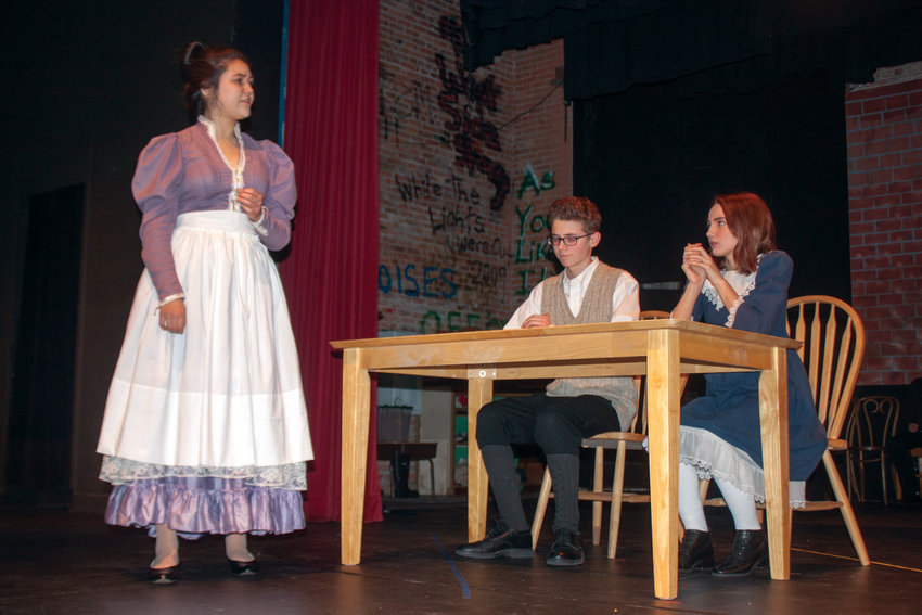 """From left, Mrs. Gibbs (Julia Neville) gets her children, George (Jackson Miller) and Rebecca (Taylor Sue Germeau) ready for school in the Port Townsend High School production of Thornton Wilder's """"Our Town."""""""
