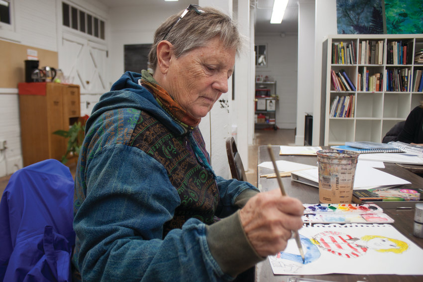 Kate Robbins watercolors a collaborative art piece.