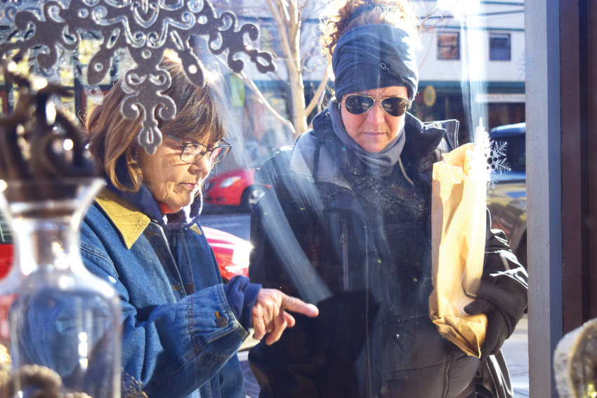 "The Friday after Thanksgiving, holiday sales are said to keep stores ""in the black,"" hence the name ""Black Friday."" In Port Townsend, Deborah Olson of Hansville and Jenna Berry of Sacramento do a little window shopping as they stroll down Water Street Friday morning."