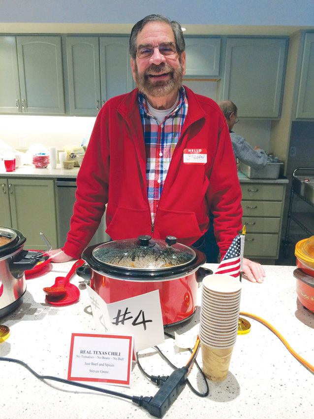 Each year, the North Bay Potluck group hosts a chili cook-off as part of more than 30 years of community building. Steven Gross shows off one of nine chilis in the competition.