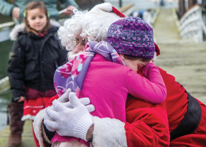 Four-year-old Juneau McKinnon gives Santa Claus a big hug as he steps off the boat and heads up the dock to the Nordland General Store on Marrowstone Island.