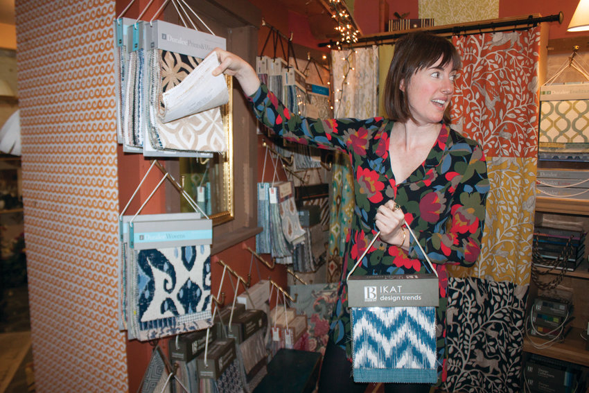 Jacqueline Mention, owner of the soon-to-be Biquette Interiors in uptown Port Townsend, turns to greet an incoming customer, as she reviews her selection of swatches.