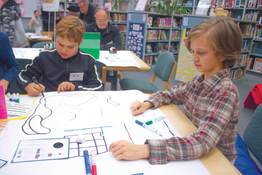 """From left, Blue Heron students Ian Rose and Tommy Magee draw paths with different colors of magic markers to direct tiny robots on white sheets of paper during the Dec. 10 """"Hour of Code"""" at their middle school."""