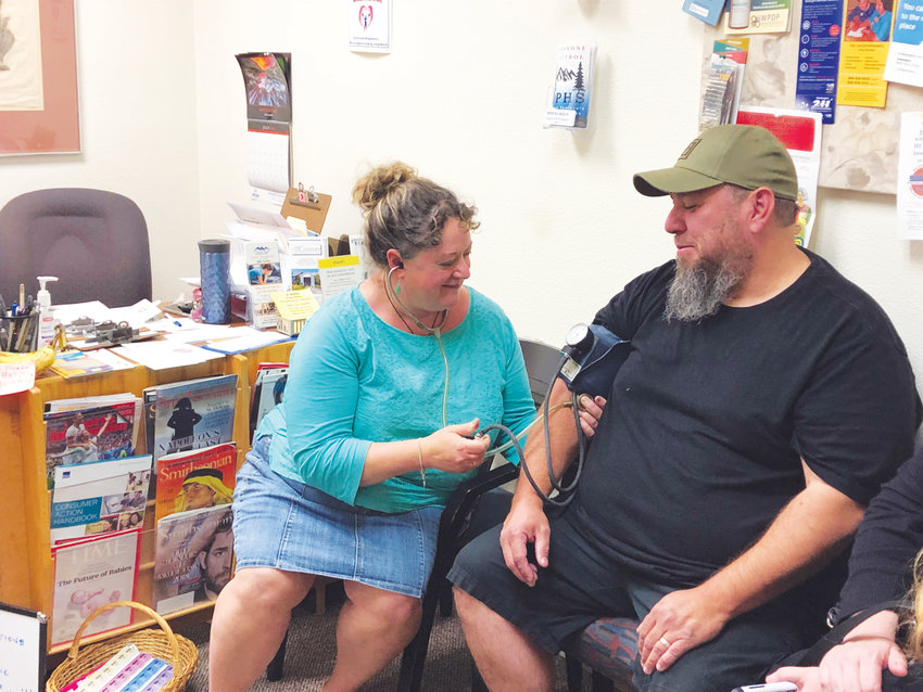 Nurse and JC MASH Acting President Christina Brinch takes the blood pressure of a client at the organization's clinic. JC MASH is fund-raising to continue offering free medical treatment to people who cannot afford it.