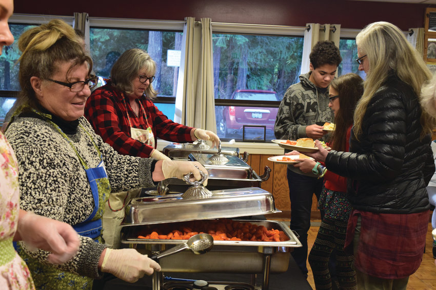 Volunteers cooked and served food, bused tables and chatted with diners during the holiday meal in Chimacum last week. Some of them have spent Christmas day this way for more than 15 years.