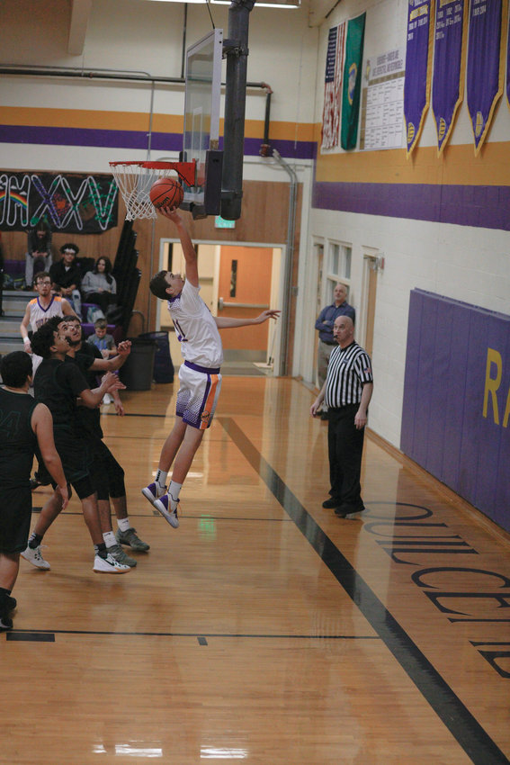 From beneath the backboard, Nathan Kieffer stretches to bounce a layup off the glass.