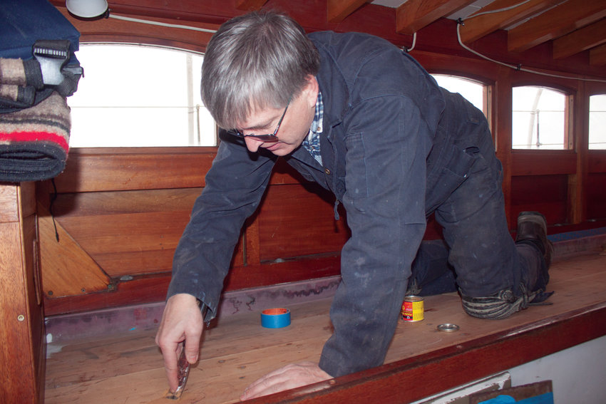 Volunteer Paul Smith applies putty to gaps between the boards of the Schooner Adventuress Jan. 18, to prepare its decks for paintwork.