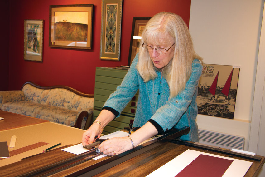 """The Big Picture"" co-owner Linda Dugan believes in measuring twice (at least) and cutting once when she makes her custom frames, which passersby can watch her do through the large storefront window at 823 Washington St. in downtown Port Townsend."