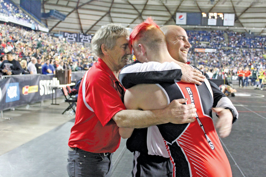 Dylan Tracer embraces wrestling coaches Steve Grimm and Jim Wilcox after winning his match in the state championships. Tracer took home 2nd place in state at the Mat Classic tournament on Feb. 22., despite wrestling with a broken nose.