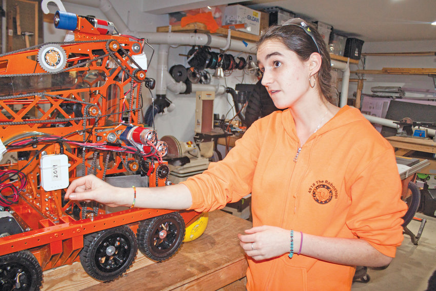"Port Townsend FIRST Robotics Competition ""Roboctopi"" President Olivia Morningstar explains how her team's robot works during an open house at their building lab on Feb. 26."