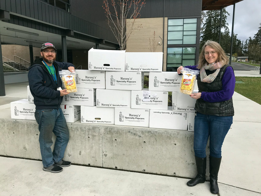 Members of the Port Townsend High School Music Boosters proudly display the 16 cases of kettle corn they donated to the child care program at Salish Coast Elementary.
