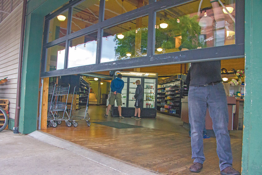 Cashier Sam Hobart closes the Aldrich's Market patio door on Tyler Street on the last day of the store's 125-year run. Coronavirus was the tipping point, owner Scott Rogers said, for the business that had not turned a profit since the end of the 2019 summer season.