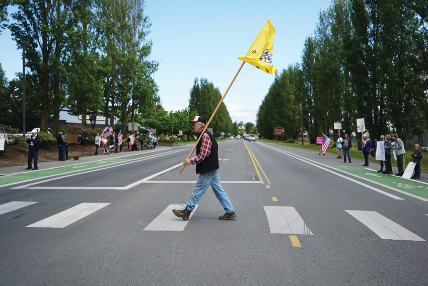 "Larry Hovde carries a ""Don't Tread on Me"" flag as he crosses Sims Way with people protesting government restrictions due to the coronavirus. ""I think it's time for another revolution. We need to go back to the principles that established this nation. We're responsible for our own health,"" he says."