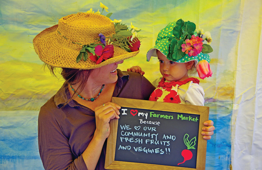 This year, shoppers at the Chimacum Farmers Market, like Naomi Specht and Solari, can continue to wear decorative hats, but must accompany them with face masks.