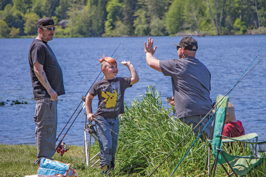 Jackson Cantrell, 7, high-fives his father Billy after helping catch a fish at Lake Leland. Jackson said he has been fishing since he was 3 and was happy to get out of Bremerton for a day of fishing in Quilcene.