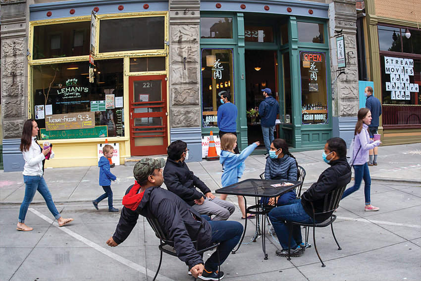 """Masked people wait for takeout from nearby restaurants on Taylor Street, a spot that would normally be full of parked cars and traffic. A portion of the street was closed to traffic over Memorial Day weekend as part of the city's """"Open Streets Initiative,"""" in an effort to start a conversation about the use of outdoor space in Port Townsend."""