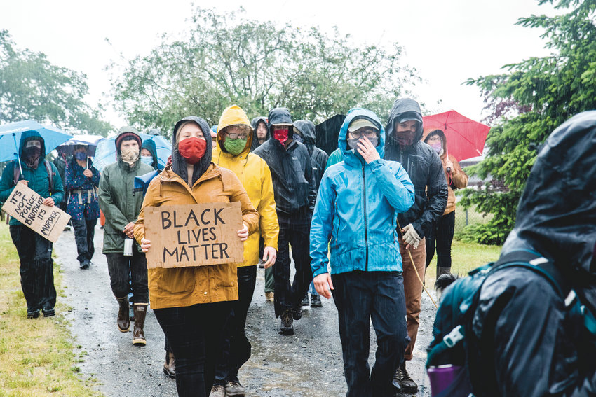 In the pouring rain, a group of 50 begins walking from Finnriver Farm. The 8.5-kilometer walk was organized to honor and remember Black, Indigenous, and people of color who have been killed by police.