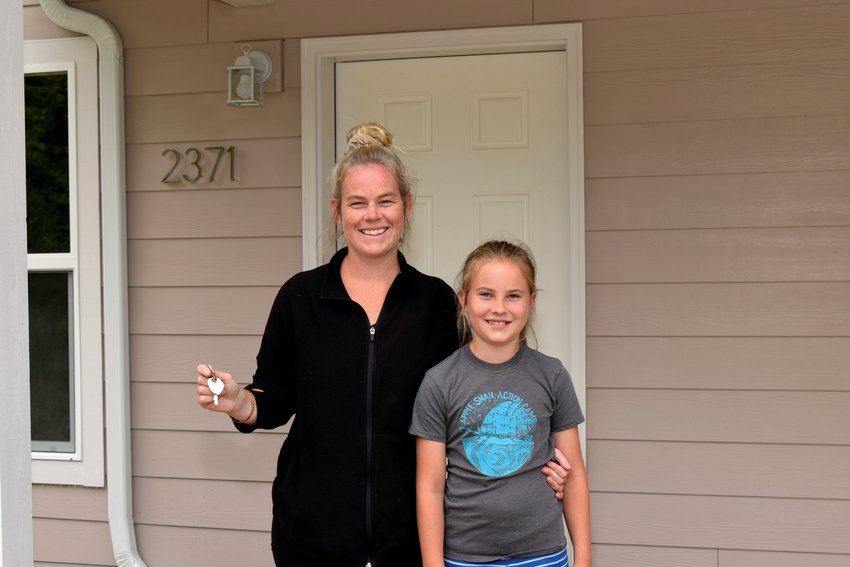 Ingrid Jonland and her daughter Olivia with the keys to their new house, made possible by John and Beth Weaver and Habitat for Humanity.