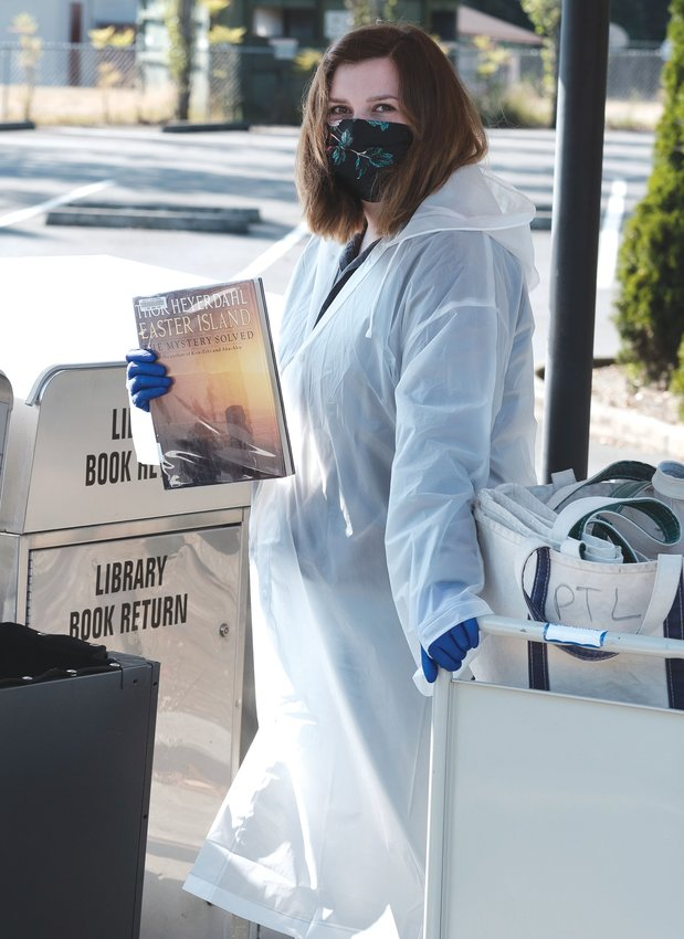 Megan Music, Jefferson County Library page, wearing protective gear while collecting materials that were returned in book drops. All materials go directly into quarantine for 96 hours before staff process items to loan again, according to library officials.