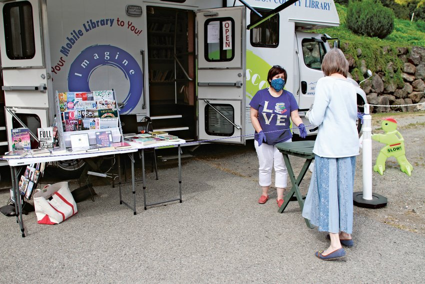 Jefferson County Library bookmobile staffer Kristin Hill assists a patron last week at the Port Ludlow Village Market stop.