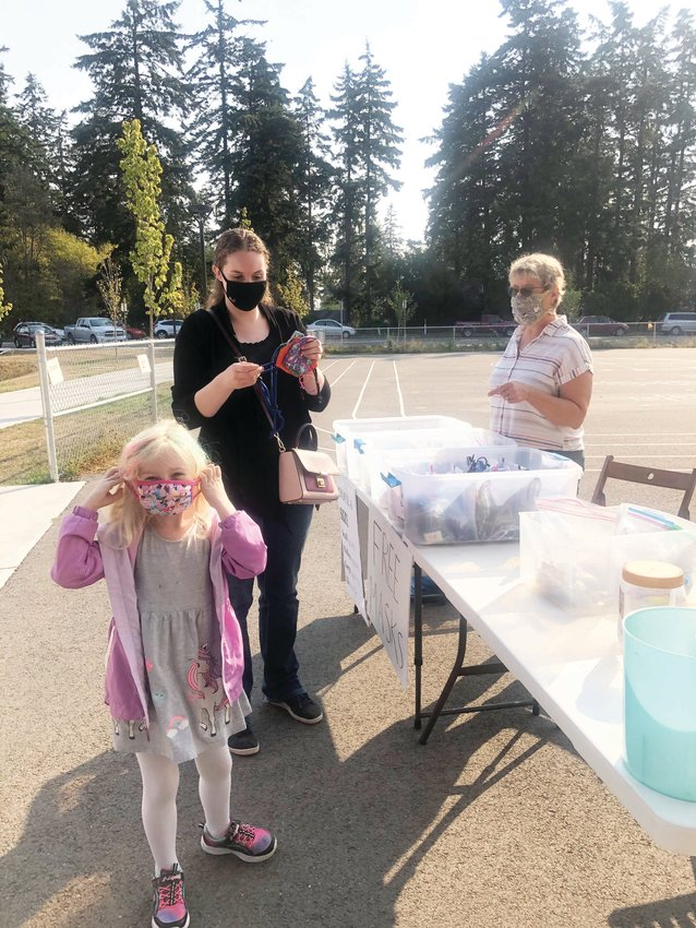 Megan Eisenman and her daughter Lily receive masks made for the students and families of Salish Coast Elementary School by volunteers with Face Mask Challenge Port Townsend.
