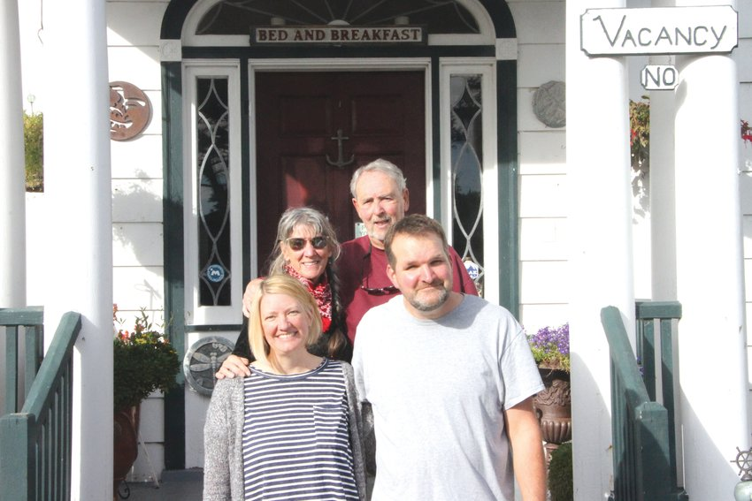 Natalie Dionne, Gail Oldroyd, Jim Oldroyd and David Dionne stand at the front steps to the Commander's Beach House, a bed-and-breakfast located on the water at Point Hudson.