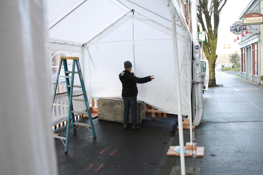 Kris Nelson, owner of several Port Townsend bars and restaurants, erects an outdoor dining shelter in front of Sirens on Water Street.
