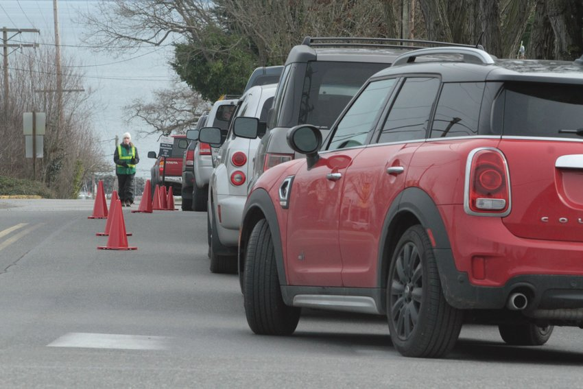 Drivers wait in a queue for COVID-19 vaccinations outside Jefferson Healthcare Friday in Port Townsend.