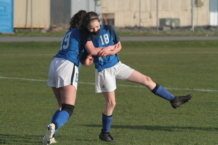 Ava Shiflett is corralled by teammate Macy Smith after her goal against Sequim.