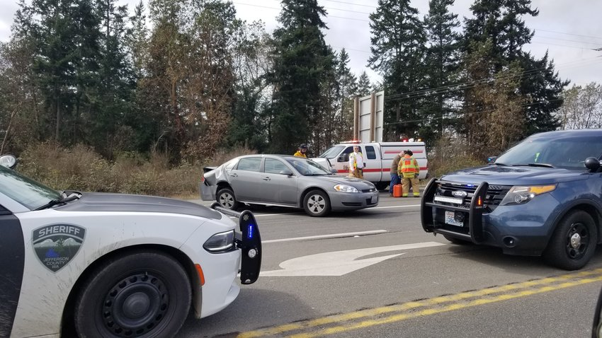 Emergency responders stand near a 2009 Chevrolet Impala that was rear-ended in a two-car collision Saturday afternoon south of Port Townsend.