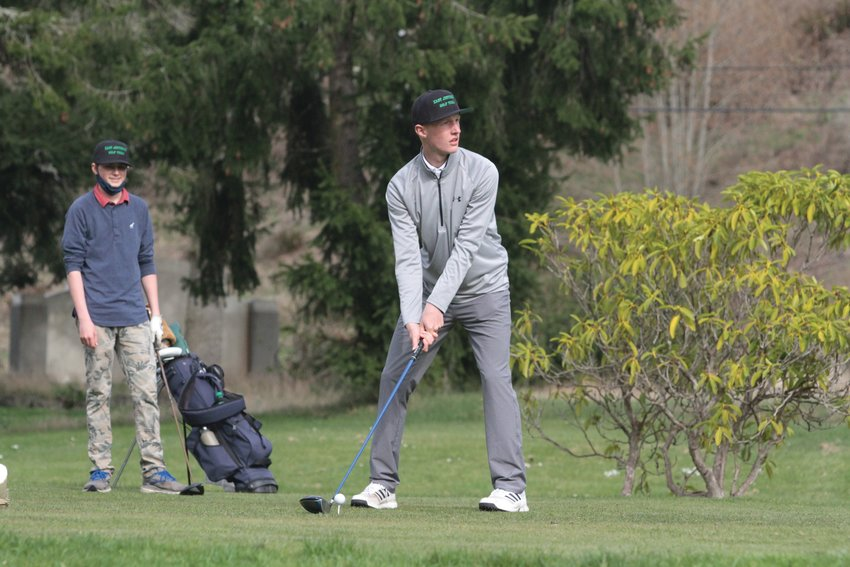 Cade Martin of the East Jefferson boys golf team tees off at the Port Ludlow Golf Course while teammate Braley Phillips watches.