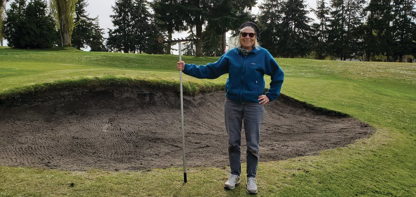That is not agolfclub in her hand. Port Townsend Women'sGolfClub captain, Katherine Buchanan spent last Friday as a volunteer repairing the bunker on hole No. 3.