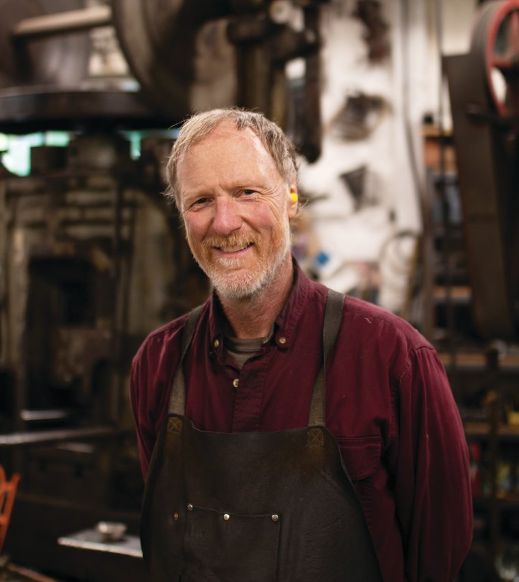 Jim Moore pauses work for a portrait in his metal shop.
