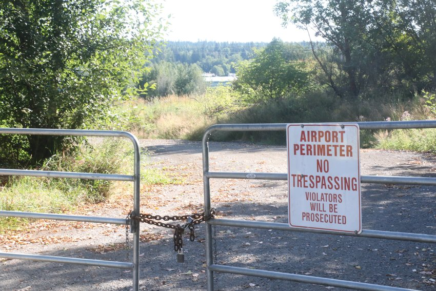 A locked gate and signage blocks off the entrance to an airport property owned by the Port of Port Townsend.