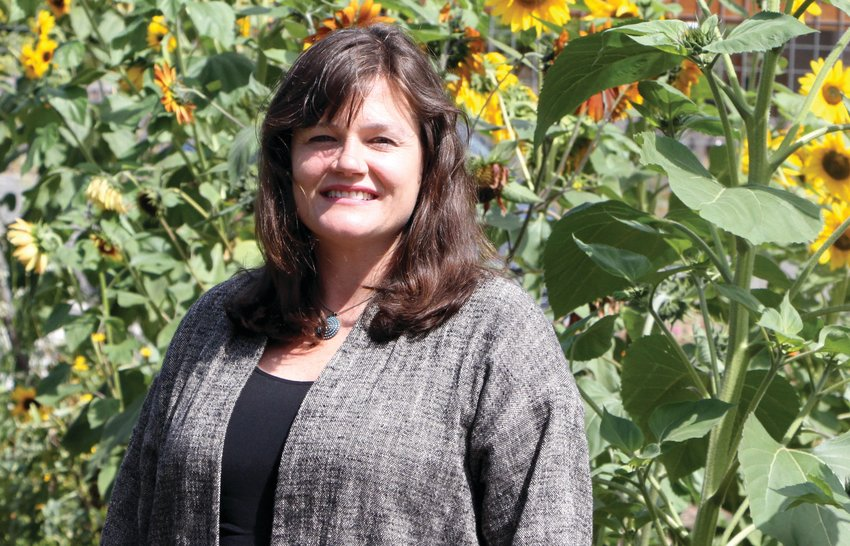 Rosenbury poses in front of the sunflowers at Salish Coast Elementary School's teaching garden, an integral setting for her place-based learning program.