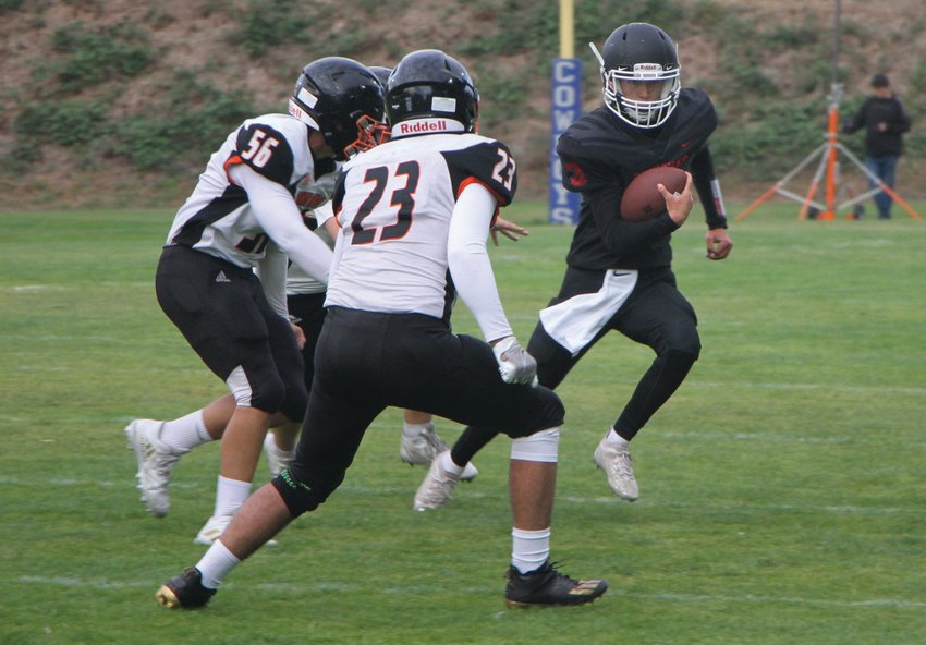 Rivals quarterback Cash Holmes evades defenders as he runs to the sideline for a first down. The Port Townsend High School sophomore scored a 10-yard touchdown run in the first quarter of the game.