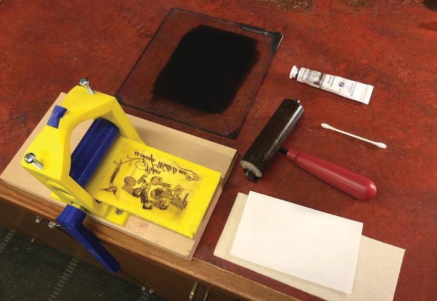 The inked plate is covered with the sheet of paper, and rolled through the press, creating an impression.