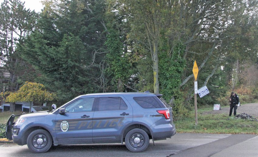 Port Townsend Police Officer Nathan Holmes stands near a tree where a man was found hanging Wednesday morning near Sheridan and Seventh streets.