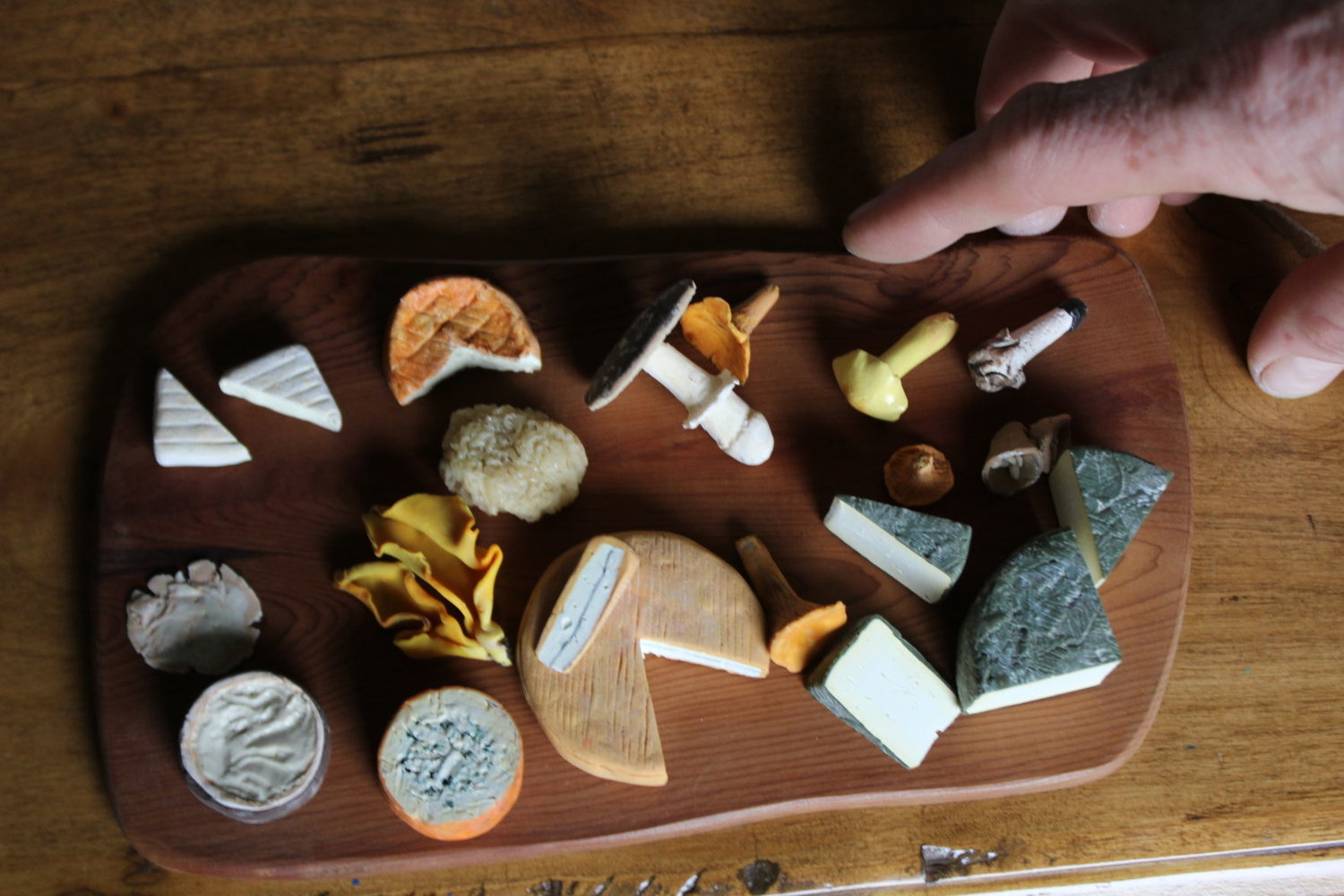 Artist Dylan Stanfield draws from his knowledge as a cheesemaker to create his miniatures. Even though they are made of clay and the size of a quarter, they look edible.