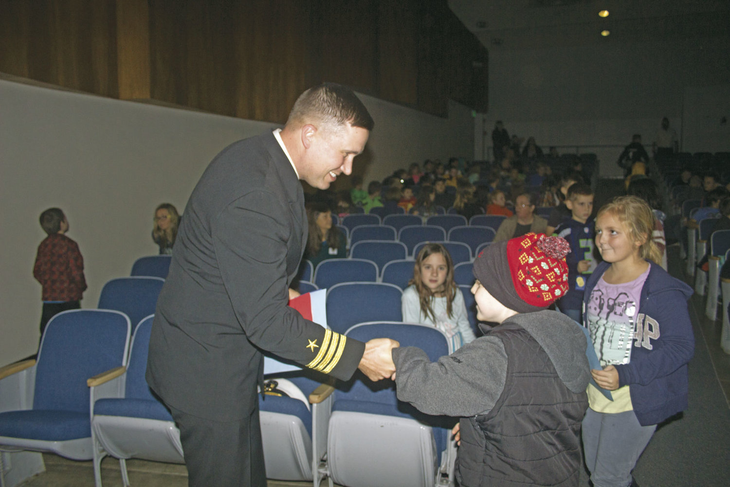 Navy Cmdr. Steve Everhart, the installation executive officer for Naval Magazine Indian Island, shakes hands with students at the Chimacum High School auditorium during their Veterans Day assembly Nov. 9.