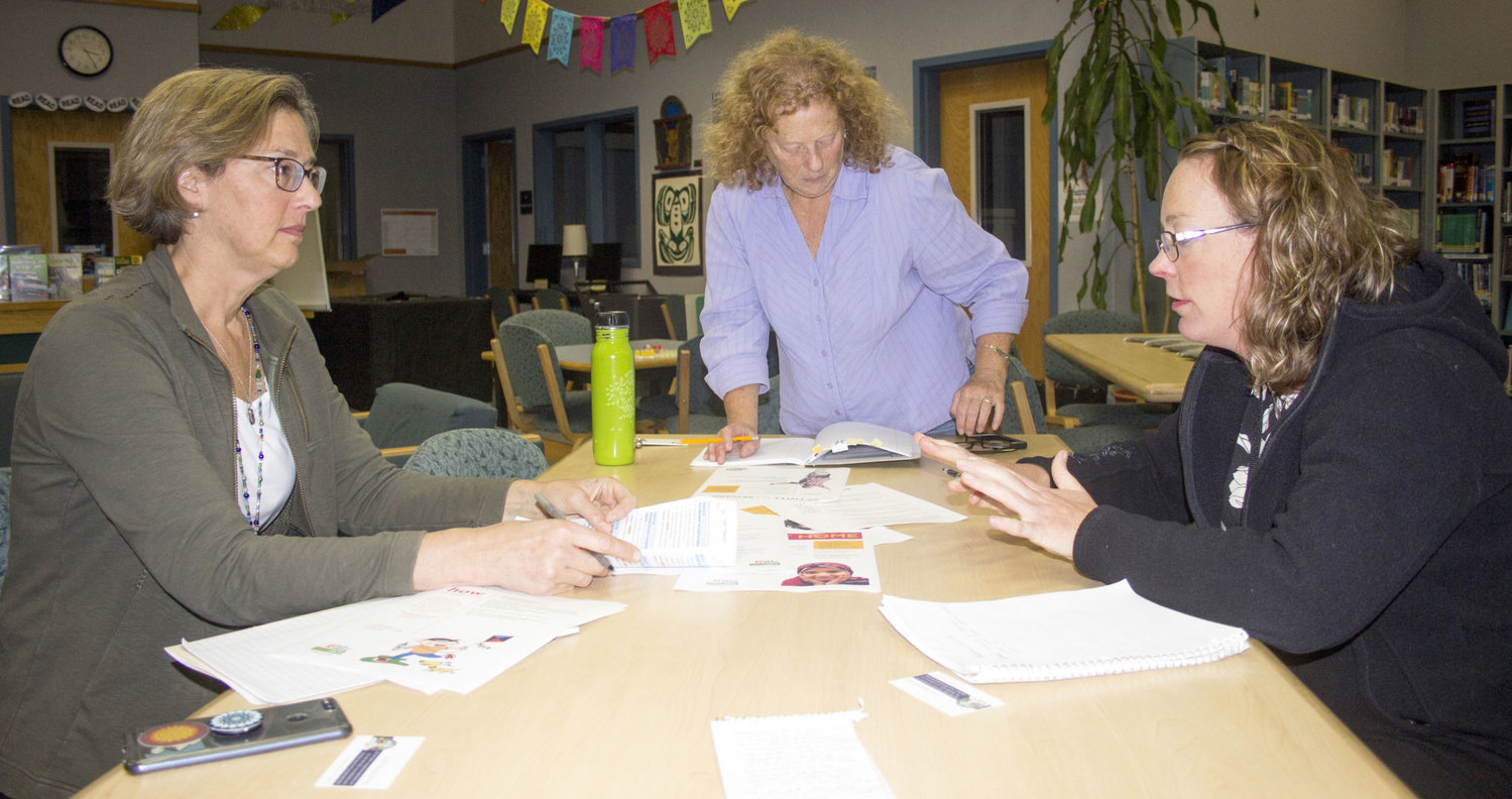 From Left, Karen Obermeyer, Julia Russell and Stacey Larson review the Port Townsend Wellness Committee's long-term goals Sept. 18. Photo by Kirk Boxleitner