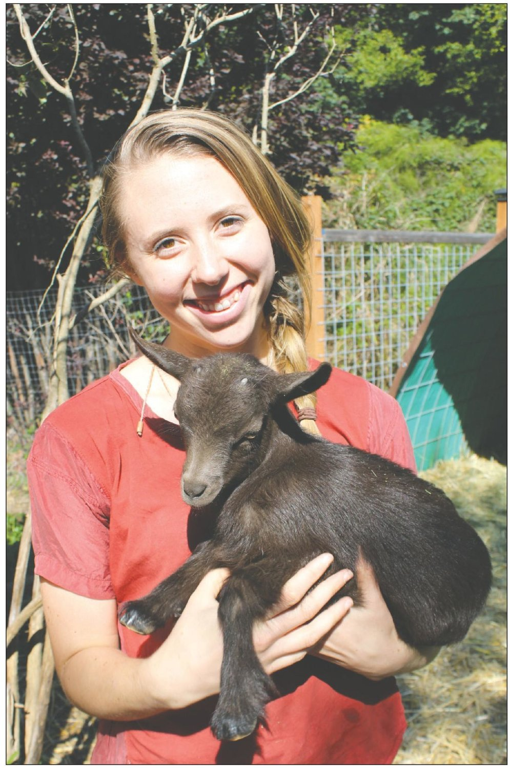 Grace Thompson, co-owner of Kodama Farm & Food Forest holds one of their baby goats they are raising to eventually make goat cheese.