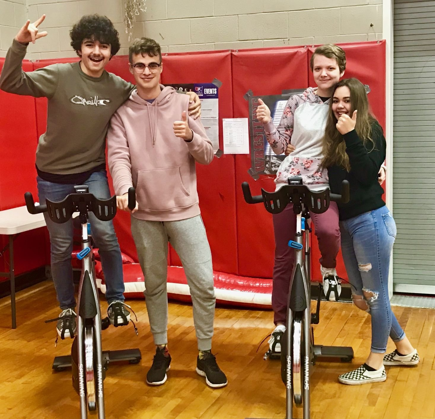 Port Townsend High School students, pictured left to right, Ian Linn-Glasgow, Roland Donanberg, Mackenzie Lake and Carly Rogers, shows off a couple of the spin bikes donated to the spin class offering a healthy outlet for students.