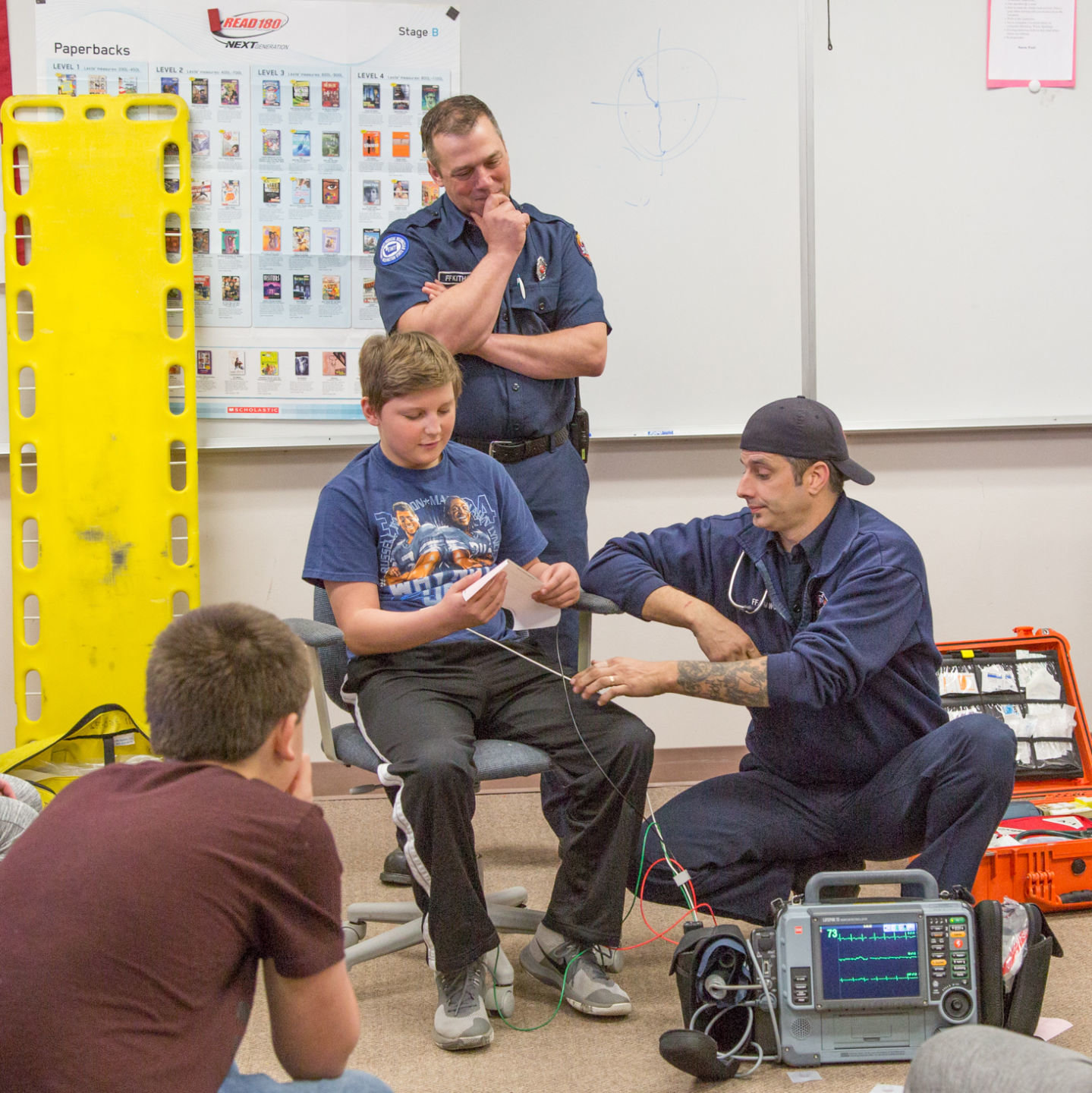 East Jefferson Fire Rescue Firefighters Mike Kithcart (standing) and Jeff Woods (kneeling) demonstrate administering an EKG with the help of student Conner Kerezsi. Photos courtesy Mitchel Osborne Photography